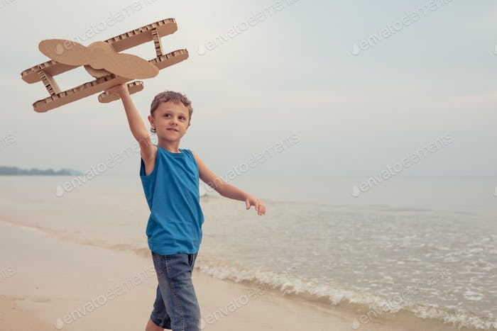 Little boy playing with cardboard toy airplane on the beach