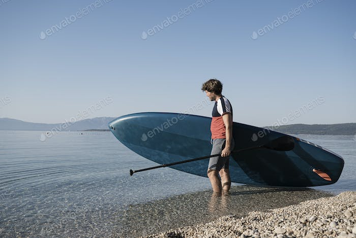 Young man carrying his stand up paddle board into the calm sea water