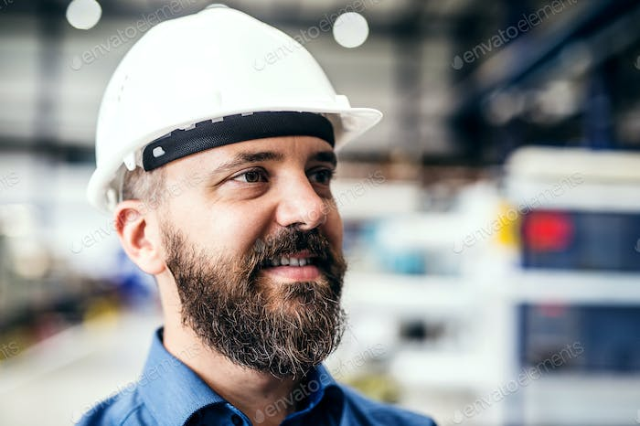 A portrait of an industrial man engineer with helmet in a factory.