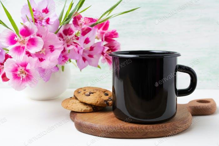 Black campfire enamel mug mockup with pink clarkia flowers