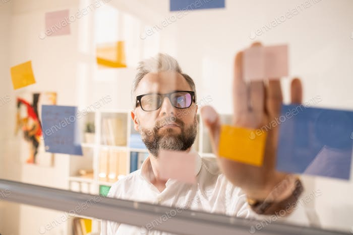 Introspective businessman joining stickers on glass