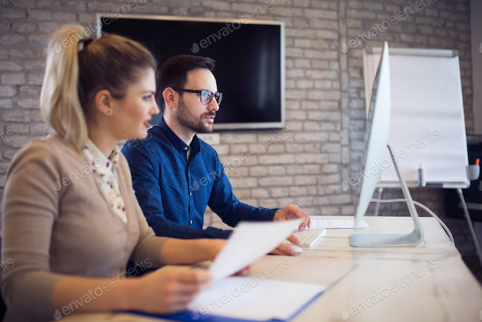 Coworking and corporate colleagues working in office