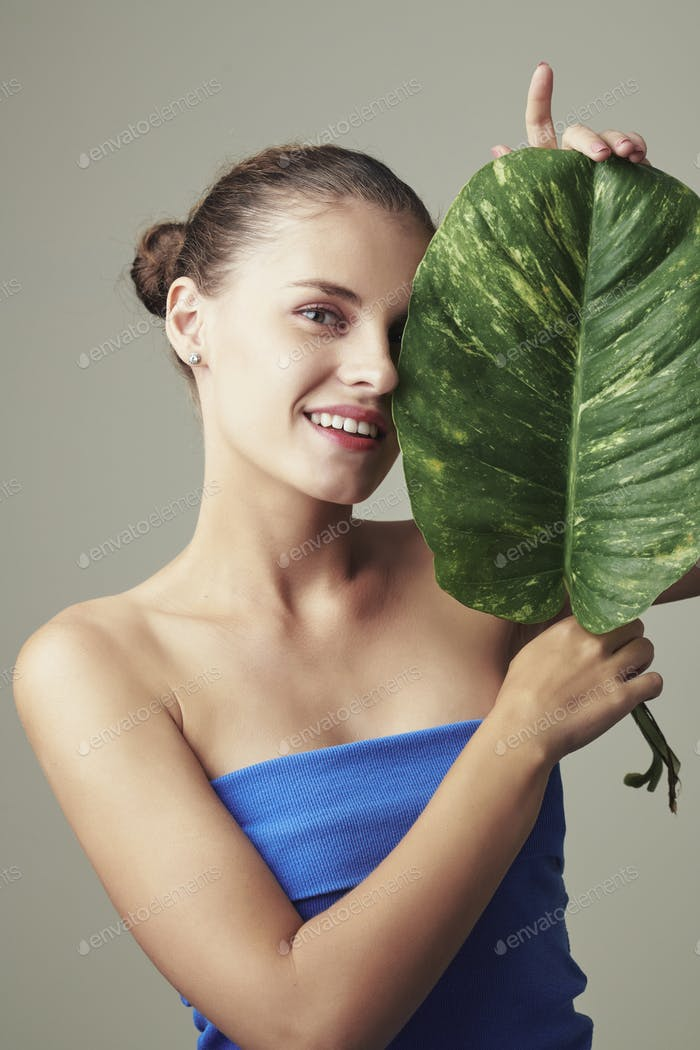 Happy woman posing with green leaf