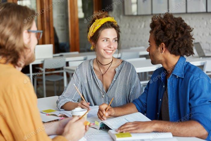 Freundliche Atmosphäre und gute Beziehungen. Multirassische Studenten machen ihre Hausaufgabe