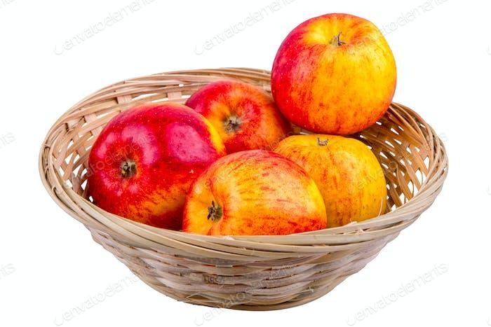 Cesta de mimbre con manzanas sobre un Fondo blanco