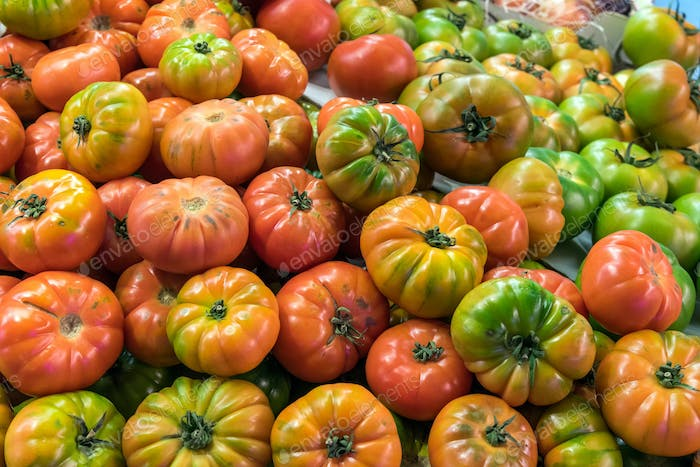 Red and green tomatoes for sale at a market