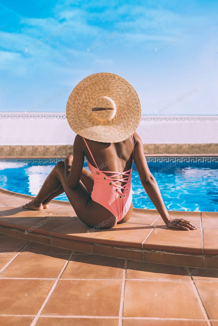 Black woman seating down in a swimming pool side