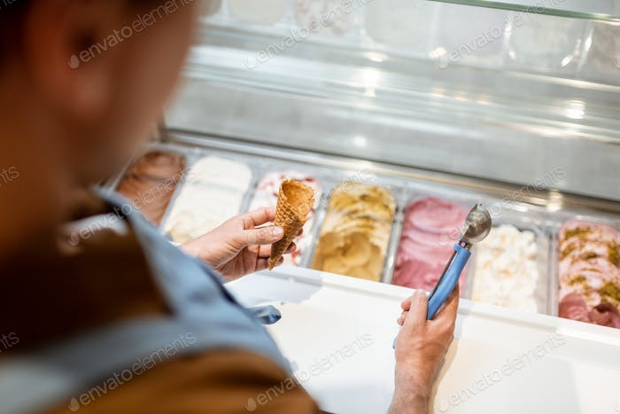 Salesman picking ice cream with a spoon from refrigerator in the shop
