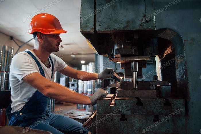 Puts sheet of metal in machine. Man in uniform works on the production. Industrial modern technology