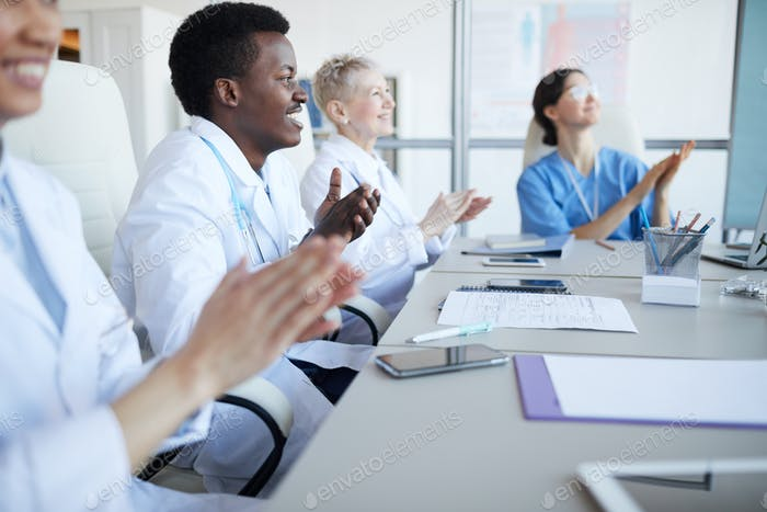 Doctors Applauding in Conference Room