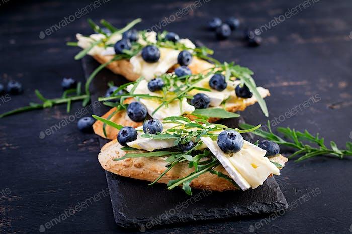 Bruschetta. Toast crostini with fresh berries blueberry and honey, brie cheese, arugula.