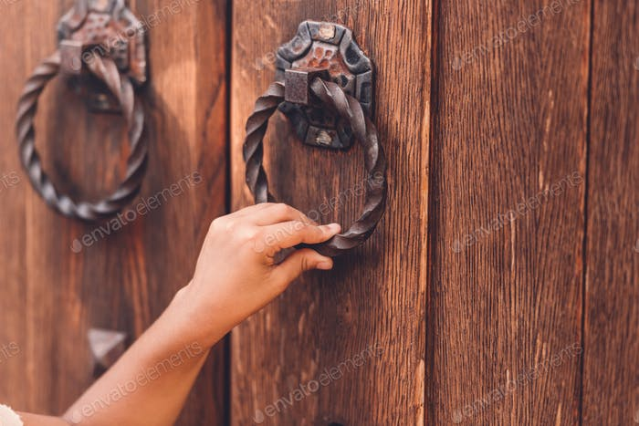 cropped view of child knocking in door with metal handle