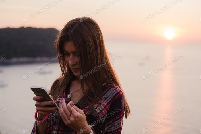 Girl using cellphone near the sea in sunrise or sunset.