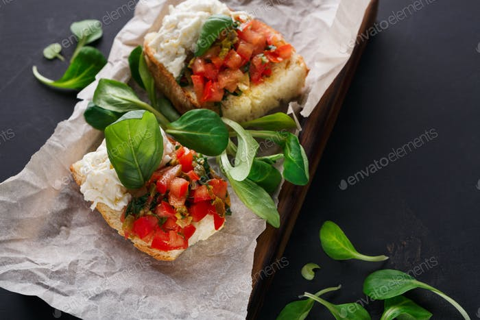 Bruschetta with cheese and vegetables on black background