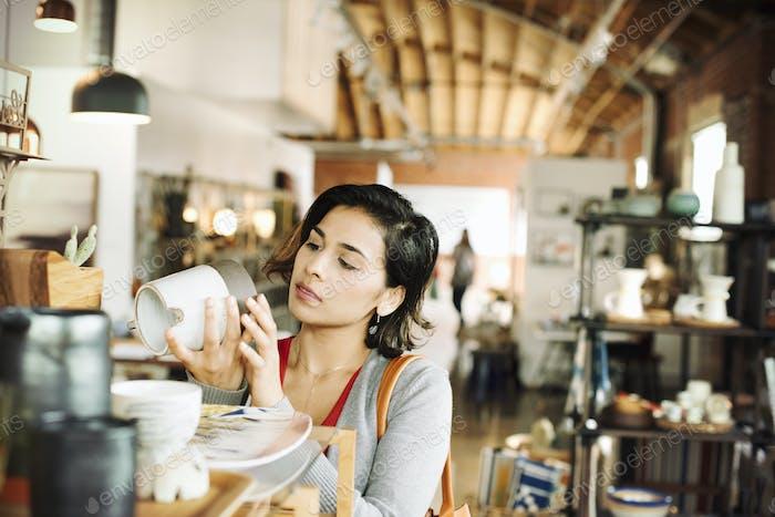 Junge Frau in einem Geschäft, Blick auf eine Keramikkrug.