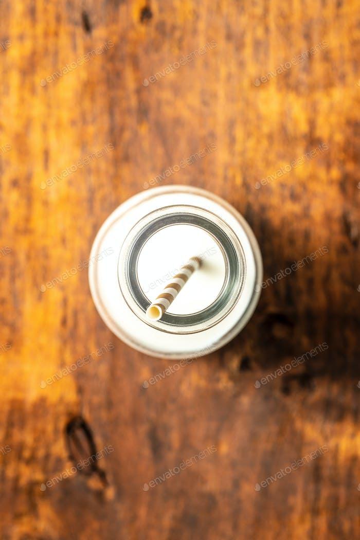 Milchflasche mit gestreiftem Stroh auf Holztisch.