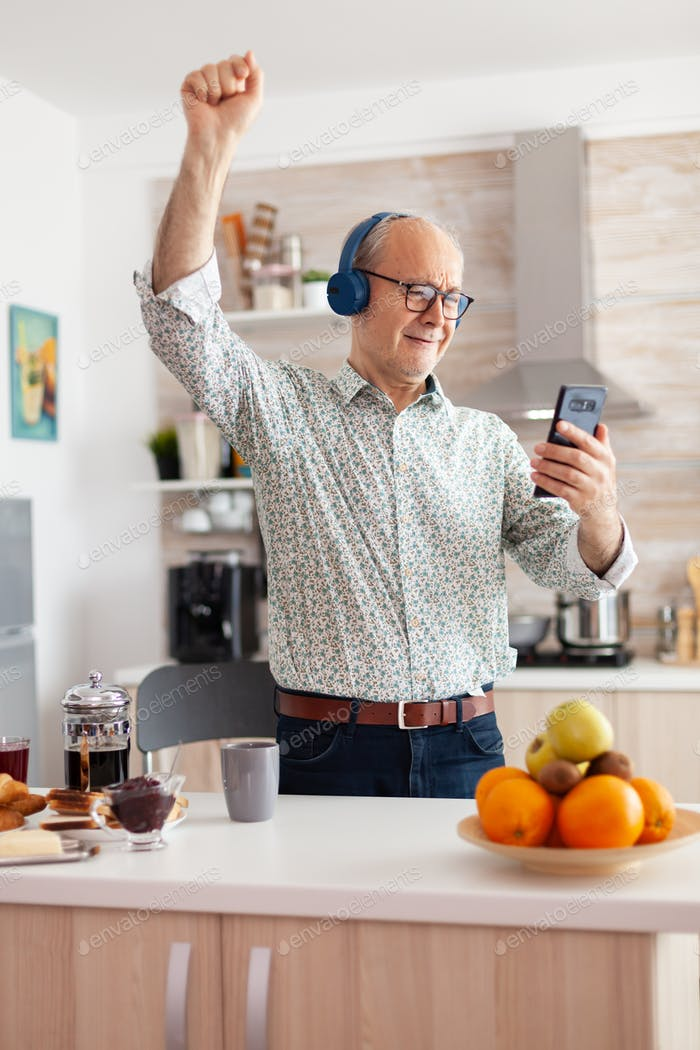 Happy mature adult listening music wearing headphones in kitchen