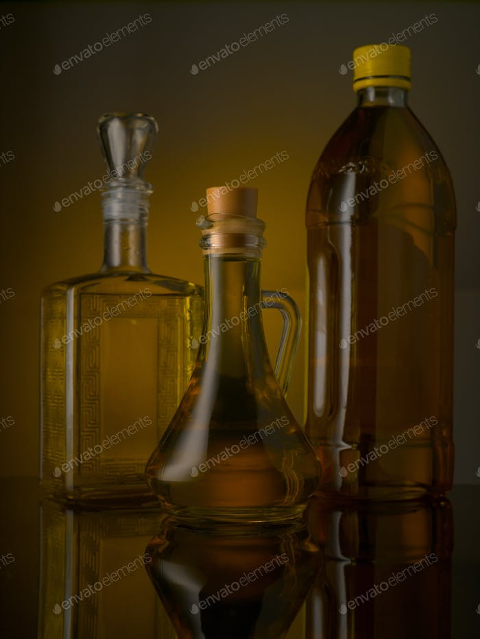 Bottles with olive and vegetable oils on a colored background
