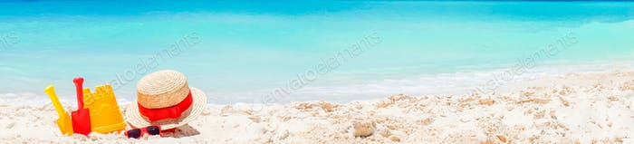Kid's beach toys on white sandy beach. Panorama of white beach