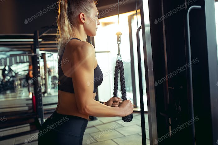 The female athlete training hard in the gym. Fitness and healthy life concept