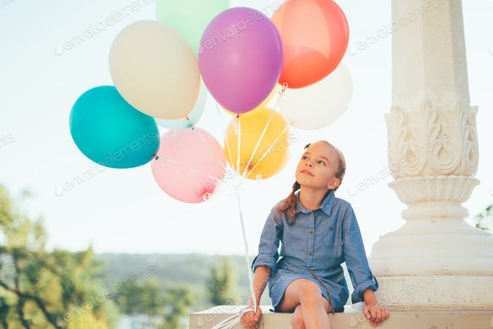 Cute girl portrait holding colorful balloons in the city park