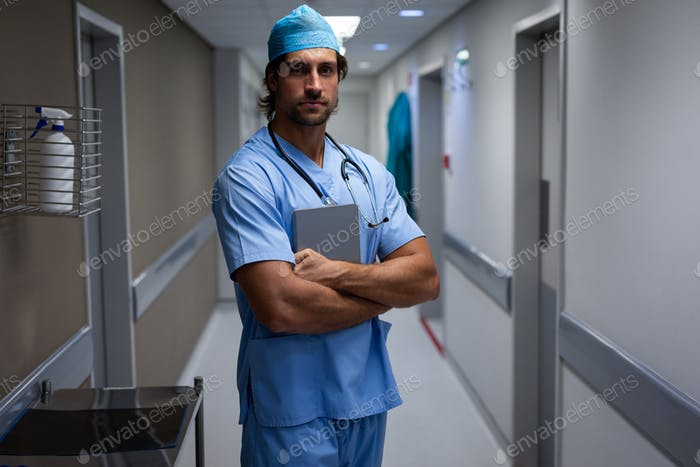 Portrait of a Caucasian male surgeon looking at the camera and standing in the corridor at hospital