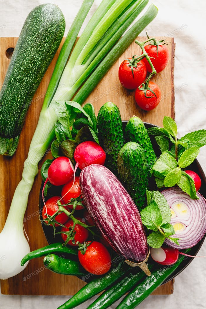 Different fresh vibrant vegetables in a plate on a wooden tray