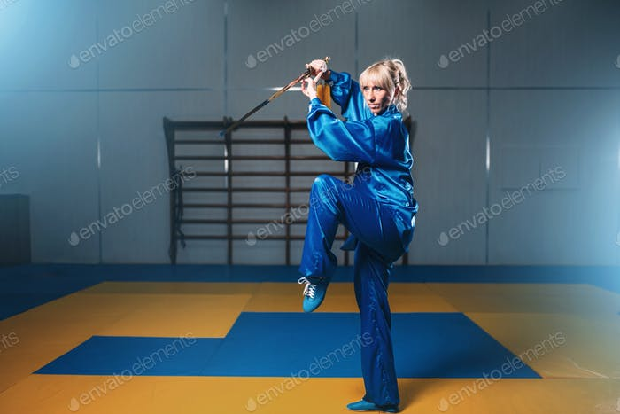 Female wushu fighter with sword in action