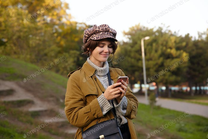 Shot of pleased young lovely brunette woman with natural makeup wearing trendy clothes