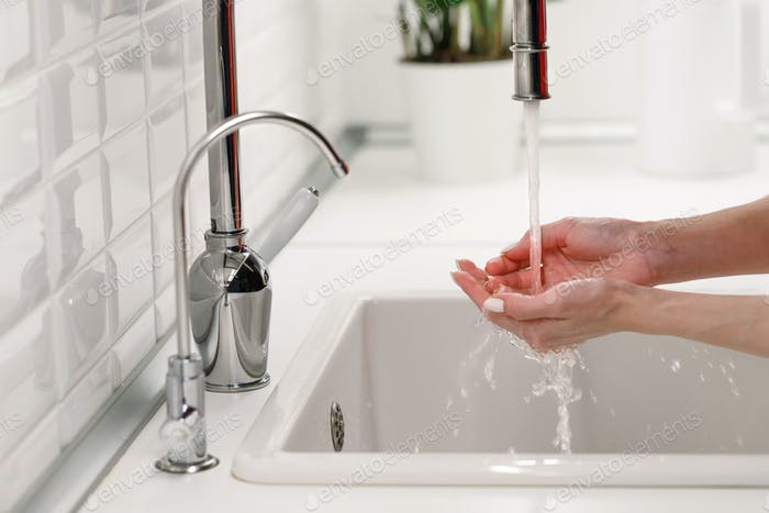 Woman washing and cleaning her hands under flowing tap water