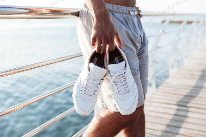 Cropped image of sportsmen hands holding sneakers at pier