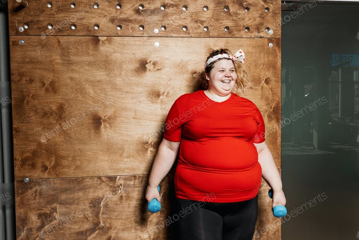 Smiling fat girl dressed in the sportswear and with a bandage on her head stands with dumbbells on