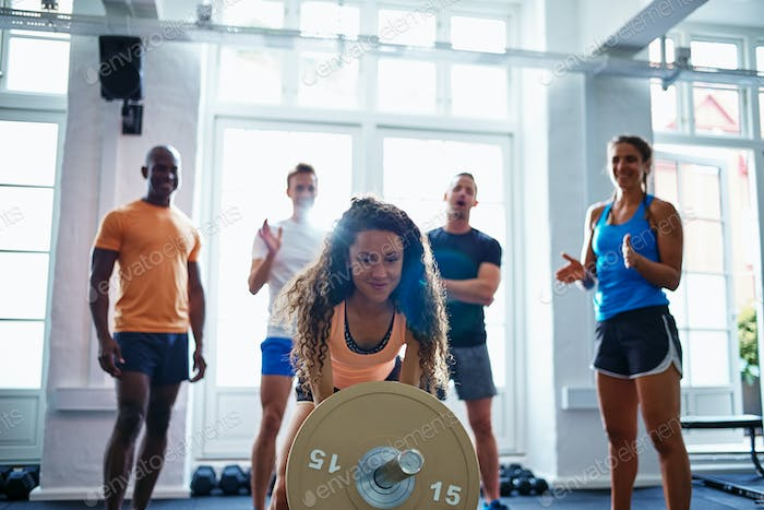 Smiling woman lifting weights with friends standing in the background