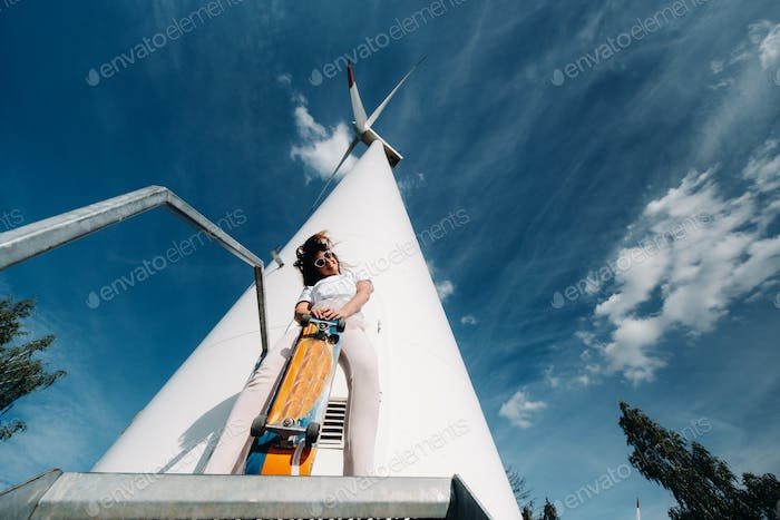 A girl in white clothes and glasses with a skate in her hands is photographed near large wind