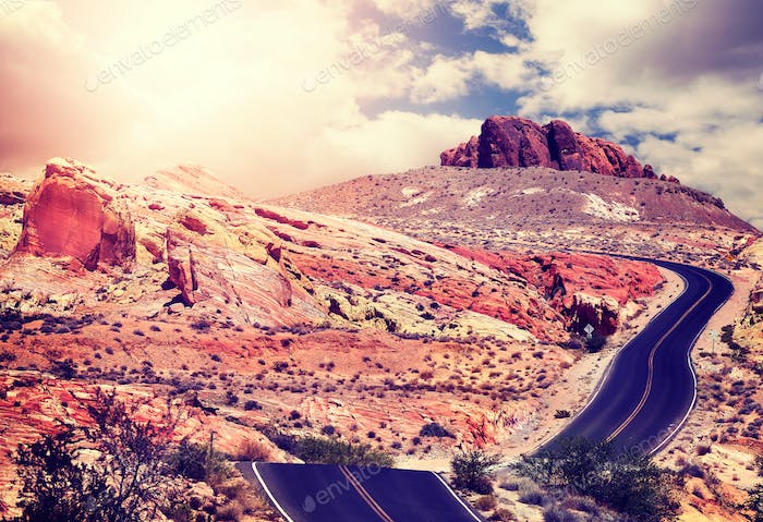 Vintage toned picture of a desert road at sunset.