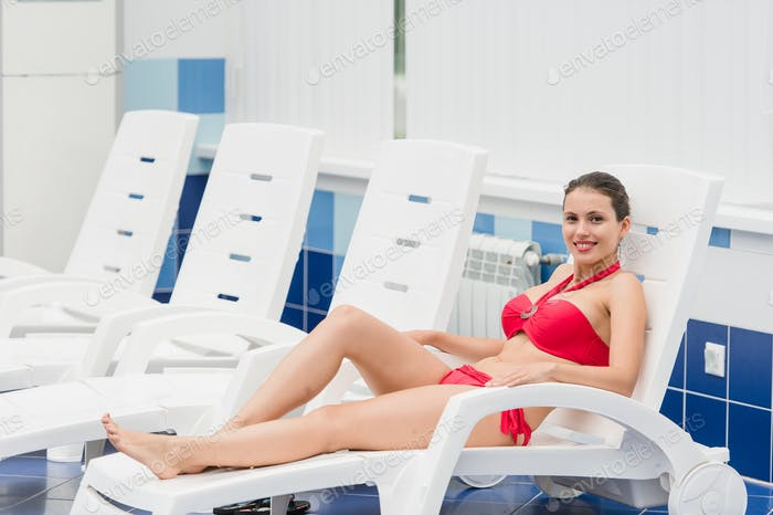 Body care. Woman with perfect body in red bikini lying on the deckchair by swimming pool at resort