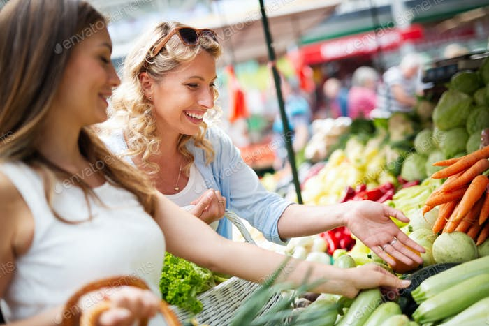 Young women friends baying vegetables and fruits on the market