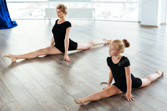 Little girl ballerina and teacher doing twine in ballet class