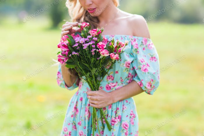 happy girl in a field with bouquet of flowers