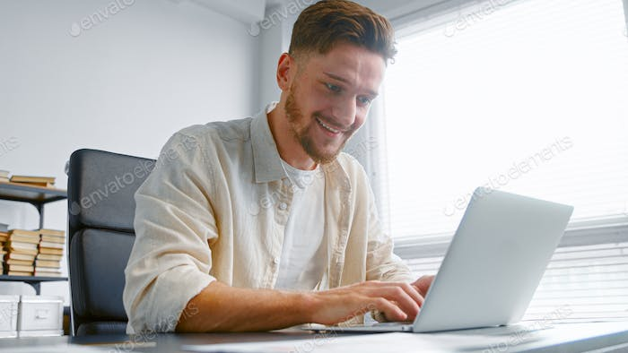 Freelancer professional bank analyst prepares contract online typing on laptop sitting at table