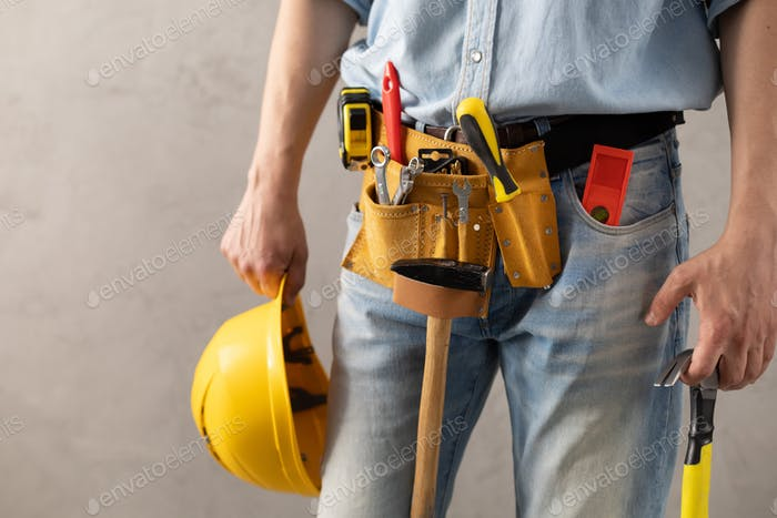 Man worker holding construction helmet and hammer tool. Male hand and construction tools
