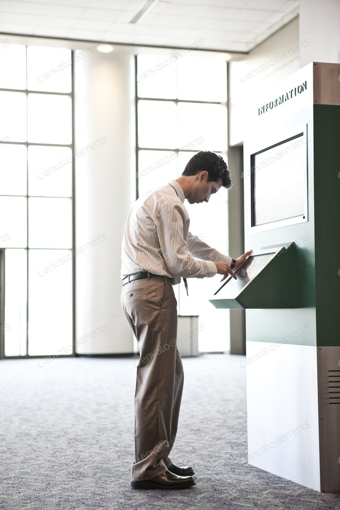 Businessman at an information kiosk in a large lobby area.