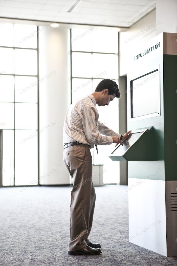 Geschäftsmann an einem Informationskiosk in einem großen Lobbybereich.