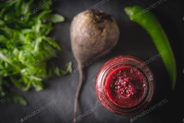 Vegetable smoothie with blurred ingredients on the dark stone background top view