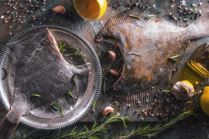Raw flounders with different seasoning on stone