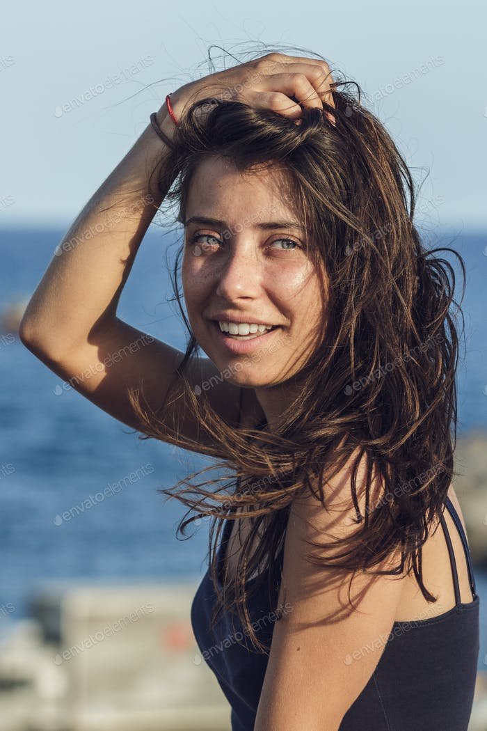 Close-up Portrait Of Cheerful Suntanned Young Woman Over Seaside Background