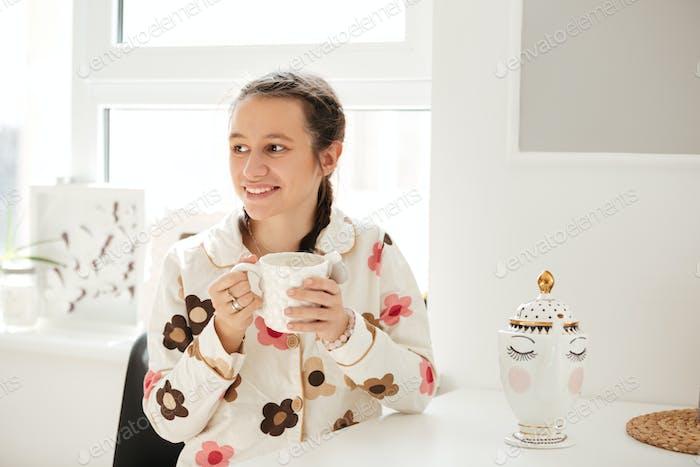 Woman wearing pajamas drinking coffee