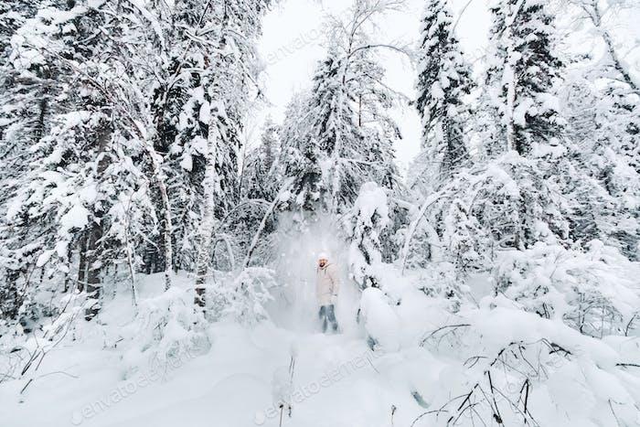 Ein Tourist spaziert in einem verschneiten Wald. Winterwald in Estonia.Reise durch den Winterwald