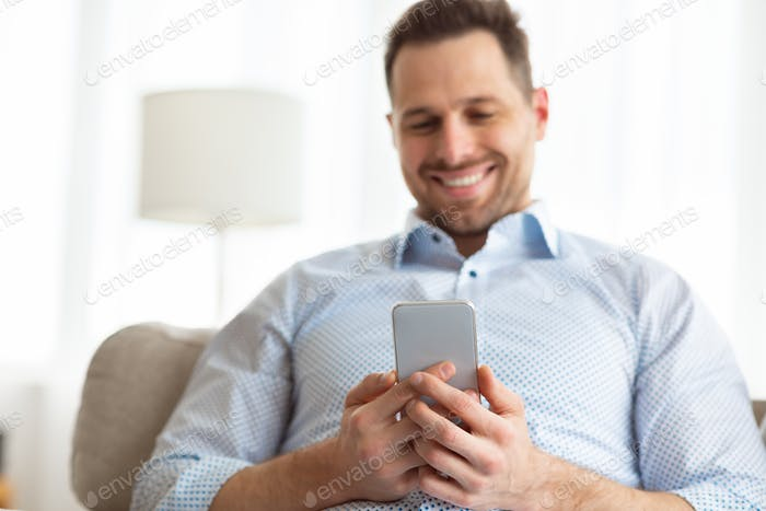 Cheerful adult man using smartphone at home