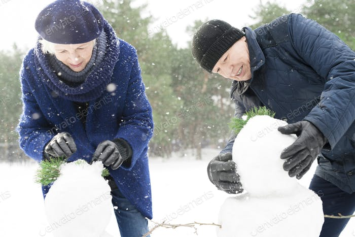 Senior Couple Building Snowman